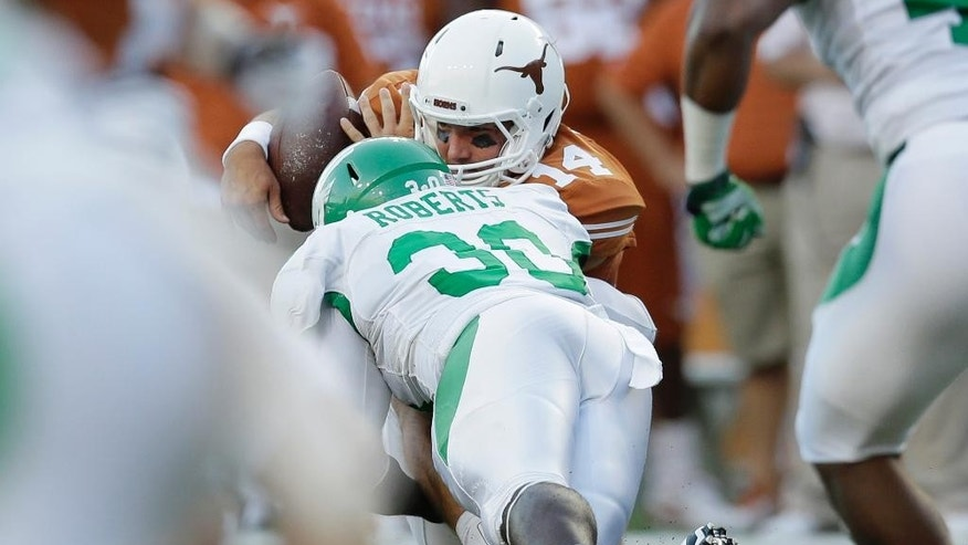 FILE- In this Saturday, Aug. 30, 2014 file photo, Texas' David Ash (14) is hit by North Texas defender Jarrian Roberts (30) as he picks up a fumble during tan NCAA college football game against North Texas in Austin, Texas.  Ash, who missed most of last season with concussion symptoms, will not play this week against BYU after getting headaches and feeling dizzy in the hours following the Longhorns' season-opening win over North Texas. (AP Photo/Eric Gay)