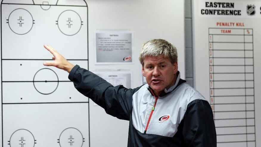 Carolina Hurricanes head coach Bill Peters speaks with members of the media during the team's NHL hockey media day in Raleigh, N.C., Thursday, Sept. 4, 2014. (AP Photo/Gerry Broome)
