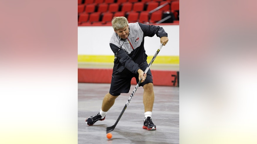 Carolina Hurricanes head coach Bill Peters demonstrates prior to a pick-up games between members of the media during the team's NHL hockey media day in Raleigh, N.C., Thursday, Sept. 4, 2014. (AP Photo/Gerry Broome)