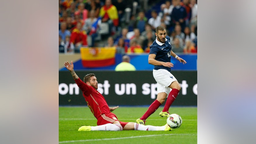 France's Karim Benzema, right, controls the ball past Spain's Sergio Ramos during their international friendly soccer match at the Stade de France in Saint Denis, outside Paris, Thursday, Sept. 4, 2014. (AP Photo/Christophe Ena)
