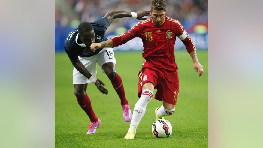 France's Moussa Sissoko, left, and Spain's Sergio Ramos battles for the ball during their international friendly soccer match at the Stade de France in Saint Denis, outside Paris, Thursday, Sept. 4, 2014. (AP Photo/Christophe Ena)