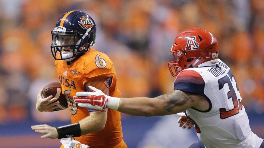 UTSA's Tucker Carter (6) is stopped behind the line of scrimmage by Arizona's Scooby Wright III during the second half of an NCAA college football game, Thursday, Sept. 4, 2014, in San Antonio. (AP Photo/Eric Gay)