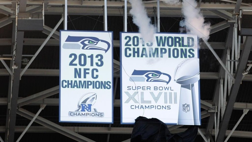 The Seattle Seahawks Super Bowl championship banner is unveiled before an NFL football game between the Seahawks and the Green Bay Packers, Thursday, Sept. 4, 2014, in Seattle. (AP Photo/Stephen Brashear)