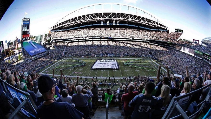 A giant Super Bowl championship banner is unfurled on the field before an NFL football game between the Seattle Seahawks and Green Bay Packers, Thursday, Sept. 4, 2014, in Seattle. (AP Photo/Scott Eklund)
