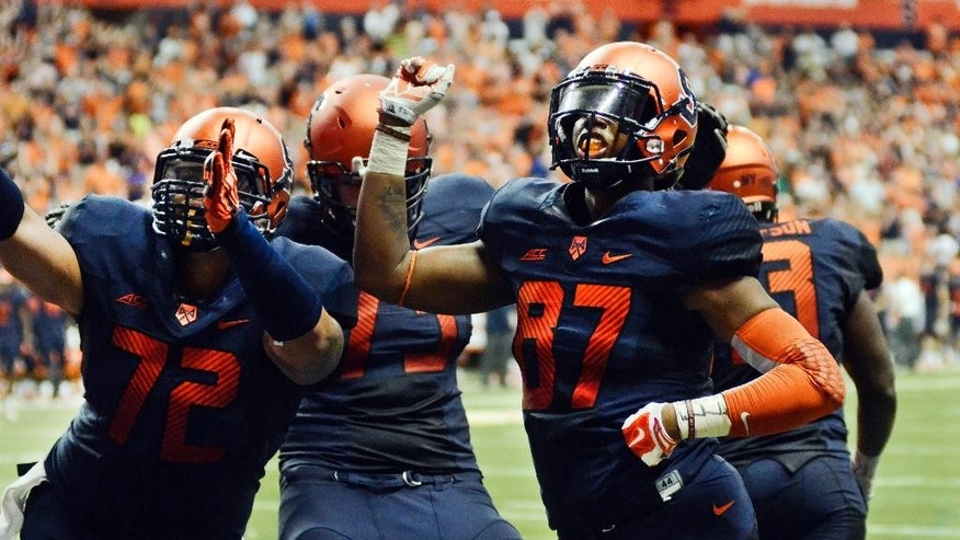 Syracuse's Kendall Moore, right, celebrates with teammates after his touchdown reception in the second overtime game Syracuse a 27-26 win over Villanova in an NCAA college football game Friday, Aug. 29, 2014, in Syracuse, N.Y. (AP Photo/Heather Ainsworth)
