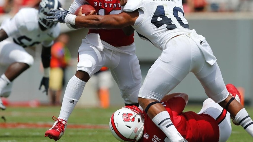 North Carolina State quarterback Jacoby Brissett, center, is tackled by Georgia Southern linebacker Edwin Jackson (40) after a run during the first half of an NCAA college football game, Saturday, Aug. 30, 2014, in Raleigh, N.C. N.C. State won 24-23. (AP Photo/The News & Observer, Ethan Hyman)