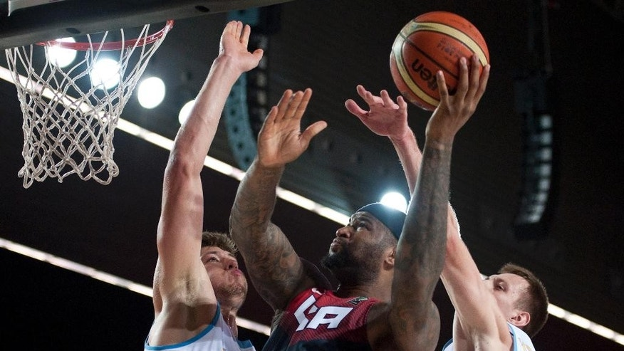 DeMarcus Cousins of the US, center, tries to dunk the ball between Ukraine's Artem Pustovyi, left, and Maxym Kornienko during the Group C Basketball World Cup match in Bilbao northern Spain, Thursday, Sept. 4, 2014. The 2014 Basketball World Cup competition take place in various cities in Spain from  last Aug. 30 through to Sept. 14.  United States won 95-71. (AP Photo/Alvaro Barrientos)