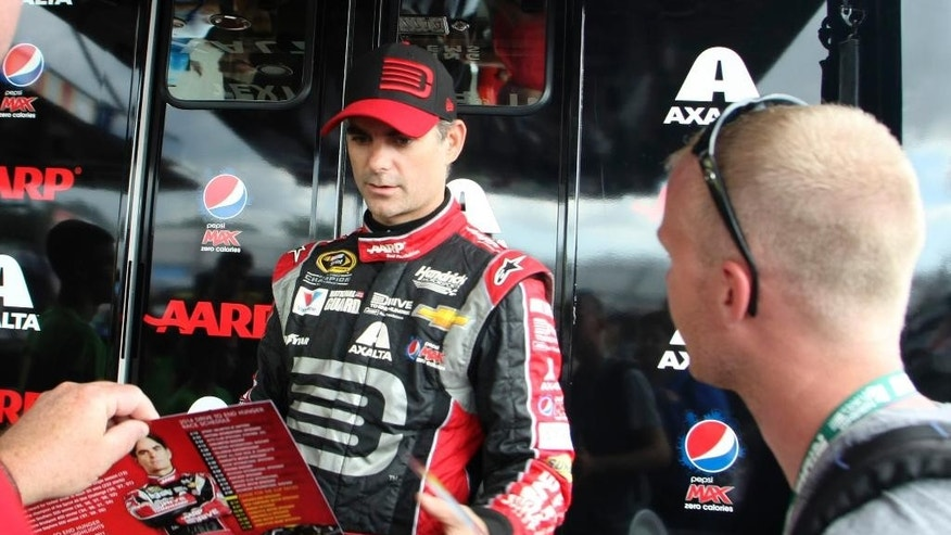 Driver Jeff Gordon signs autographs during a break in practice for Saturday night's NASCAR Sprint Cup series auto race at Richmond International Raceway, Friday Sept. 5, 2014, Richmond, Va. (AP Photo/Jason Hirschfeld)