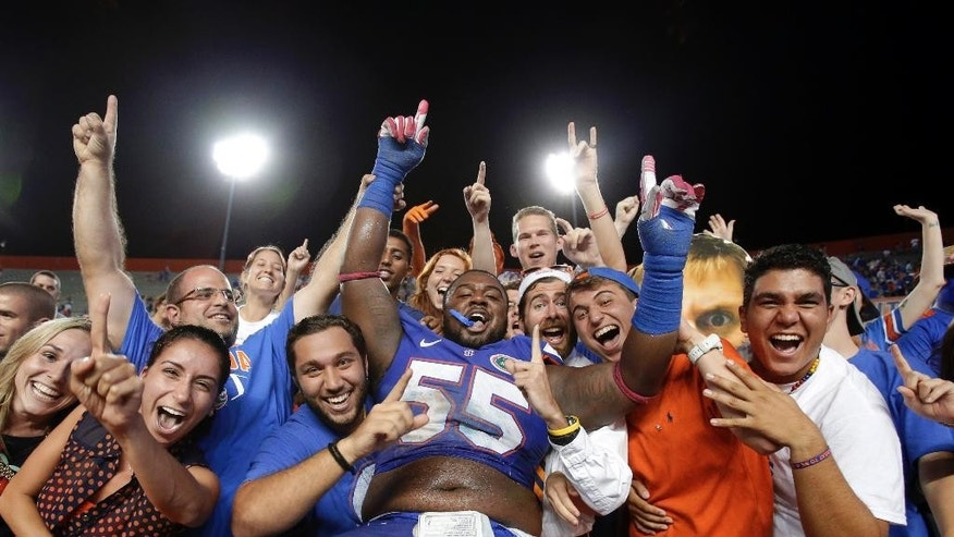 FILE - In this Oct. 5, 2013, file photo, Florida defensive lineman Darious Cummings (55) celebrates with fans after Florida defeated Arkansas 30-10 in an NCAA college football game in Gainesville, Fla. An undisclosed violation of team rules got Cummings and two teammates suspended for the opening game of the season that lasted 10 seconds before being cancelled for weather.  (AP Photo/John Raoux, File)