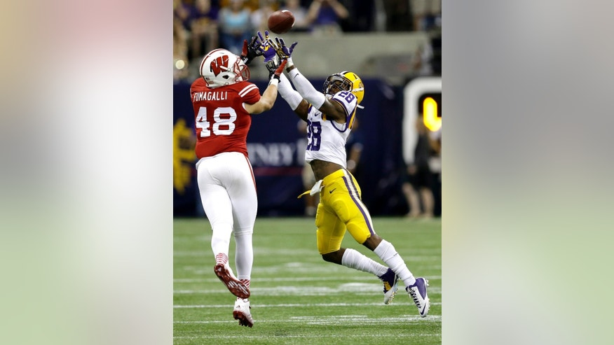 LSU safety Jalen Mills (28) intercepts a pass intended for Wisconsin tight end Troy Fumagalli during the second half of an NCAA college football game Saturday, Aug. 30, 2014, in Houston. LSU won 28-24. (AP Photo/David J. Phillip)
