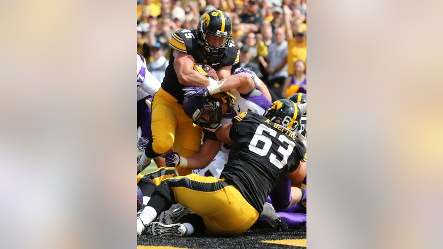 Iowa running back Mark Weisman, top, scores a touchdown during the first half of an NCAA college football game against Northern Iowa, Saturday, Aug. 30, 2014, in Iowa City, Iowa. (AP Photo/Justin Hayworth)