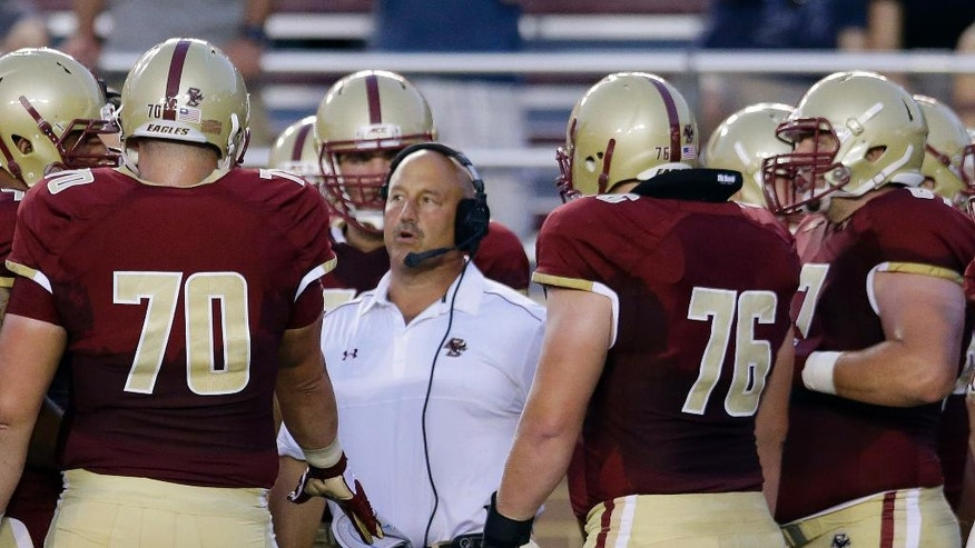 Boston College head coach Steve Addazio, center, huddles up his team on the sideline during a review of a play during the first quarter of an NCAA college football game against Pittsburgh, Friday, Sept. 5, 2014, in Boston. (AP Photo/Stephan Savoia)