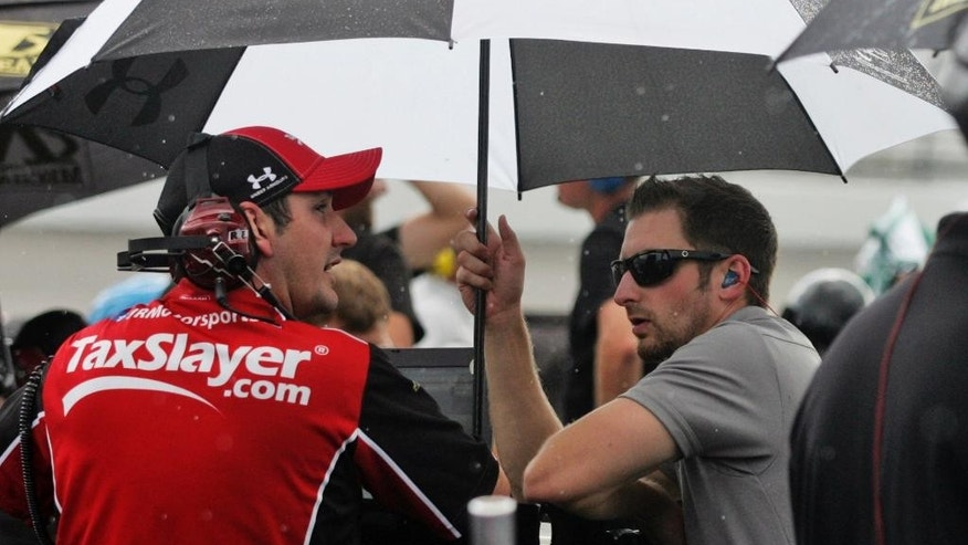 Pit crews wait under umbrellas during rain delay in qualifying for the NASCAR Nationwide series auto race at Richmond International Raceway in Richmond, Va., Friday, Sept. 5, 2014. (AP Photo/Jason Hirschfeld)