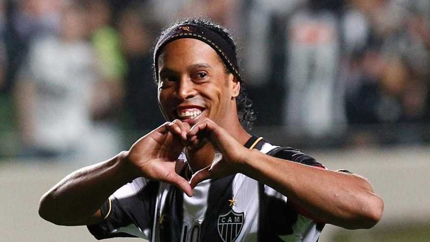 FILE - In this July 11, 2013 file photo, Brazil's Atletico Mineiro's Ronaldinho celebrates his team's victory over Argentina's Newell's Old Boys at the end of a Copa Libertadores semifinal soccer match in Belo Horizonte, Brazil. Mexico's Queretaro soccer club announced on Friday, Sept. 5, 2014 they came to an agreement with Ronaldinho for him to play on their team. (AP Photo/Bruno Magalhaes, File)