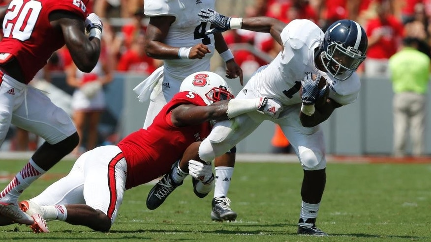 Georgia Southern running back Alfred Ramsby (1) tries to escape from North Carolina State linebacker Rodman Noel (5) during the first half of an NCAA college football game, Saturday, Aug. 30, 2014, in Raleigh, N.C. N.C. State won 24-23. (AP Photo/The News & Observer, Ethan Hyman)