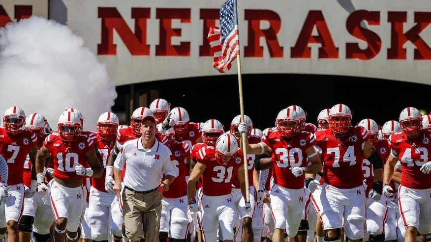 Nebraska head coach Bo Pelini leads his team onto the field prior to the first half of an NCAA college football game against Florida Atlantic, in Lincoln, Neb., Saturday, Aug. 30, 2014. (AP Photo/Nati Harnik)