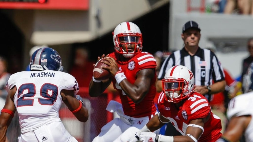 Nebraska quarterback Tommy Armstrong Jr. (4) looks to pass between Florida Atlantic defensive back Sharrod Neasman (29) and Nebraska running back Terrell Newby (34) in the first half of an NCAA college football game in Lincoln, Neb., Saturday, Aug. 30, 2014. (AP Photo/Nati Harnik)