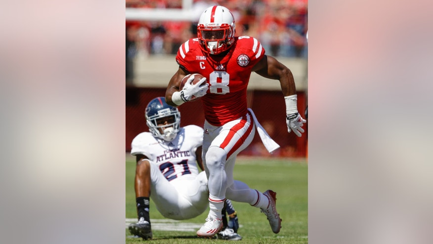 Nebraska running back Ameer Abdullah (8) runs past Florida Atlantic defensive back D'Joun Smith (21) in the first half of an NCAA college football game in Lincoln, Neb., Saturday, Aug. 30, 2014. (AP Photo/Nati Harnik)