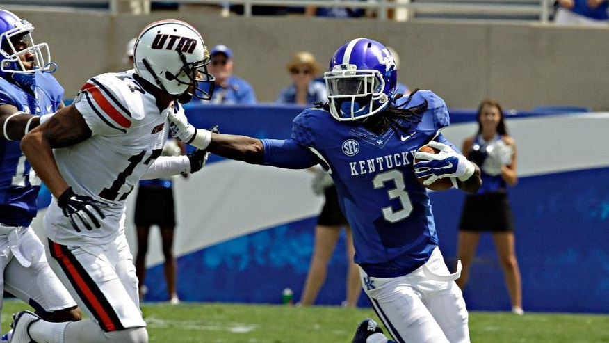 Kentucky cornerback Fred Tiller (3) fends off Tennessee-Martin wide receiver Kyle Kerrick (17) after making a pass interception in their NCAA college football game in Lexington, Ky., Saturday, Aug. 30, 2014. Kentucky beat Tennessee-Martin 59-14 to open the season. (AP Photo/Garry Jones)