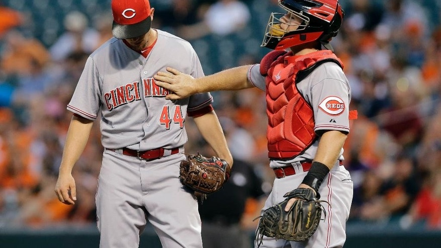 Cincinnati Reds catcher Tucker Barnhart, right, pats starting pitcher Mike Leake on the chest during a visit to the mound after Leake walked Baltimore Orioles' J.J. Hardy in the first inning of an interleague baseball game, Thursday, Sept. 4, 2014, in Baltimore. Baltimore scored six runs in the first. (AP Photo/Patrick Semansky)