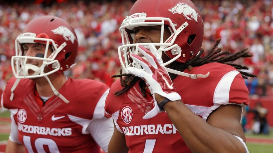Arkansas wide receiver Keon Hatcher, right, and quarterback Brandon Allen (10) return to the bench after Hatcher's touchdown in the first quarter of an NCAA college football game against Nicholls in Fayetteville, Ark., Saturday, Sept. 6, 2014. (AP Photo/Danny Johnston)