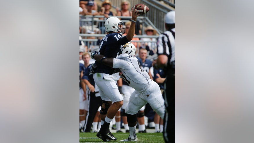 Penn State quarterback Christian Hackenberg (14) is hit by Akron defensive lineman Se'Von Pittman (90) as he releases a pass in the second quarter of an NCAA college football game against Akron in State College, Pa., Saturday, Sept. 6, 2014. The pass was incomplete. (AP Photo/Gene J. Puskar)