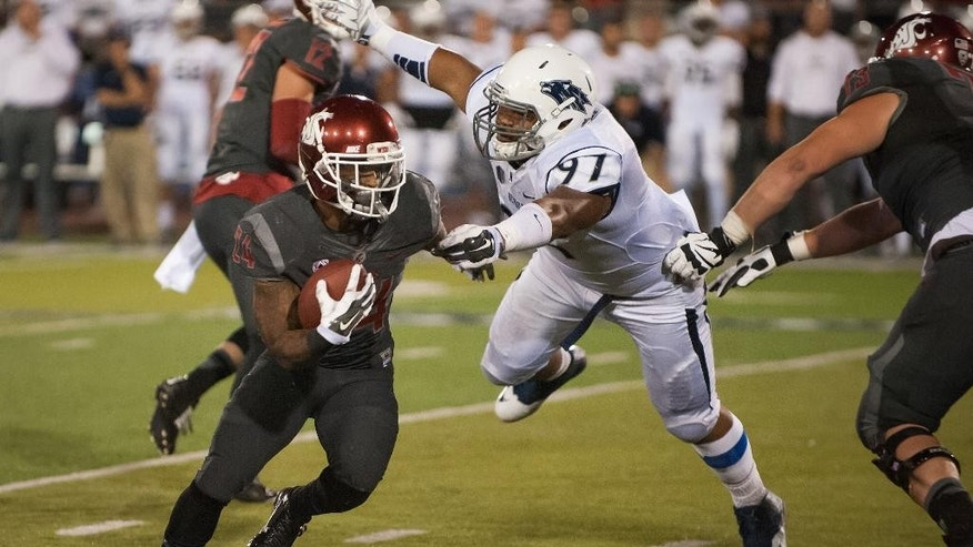 Washington State's Theron West (24) runs past Nevada's Salesa Faraimo (97) during the second half of an NCAA college football game on Friday, Sept. 5, 2014 in Reno, Nev. Nevada defeated Washington State 24-13. (AP Photo/Kevin Clifford)