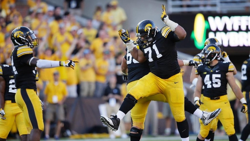 Iowa defensive lineman Carl Davis (71) celebrates with teammates after recovering a fumble by Ball State quarterback Ozzie Mann during the final seconds of an NCAA college football game, Saturday, Sept. 6, 2014, in Iowa City, Iowa. Iowa won 17-13. (AP Photo/Charlie Neibergall)