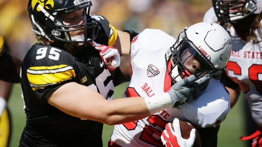 Ball State running back Jahwan Edwards, right, is tackled by Iowa defensive lineman Drew Ott (95) during the first half of an NCAA college football game, Saturday, Sept. 6, 2014, in Iowa City, Iowa. (AP Photo/Charlie Neibergall)