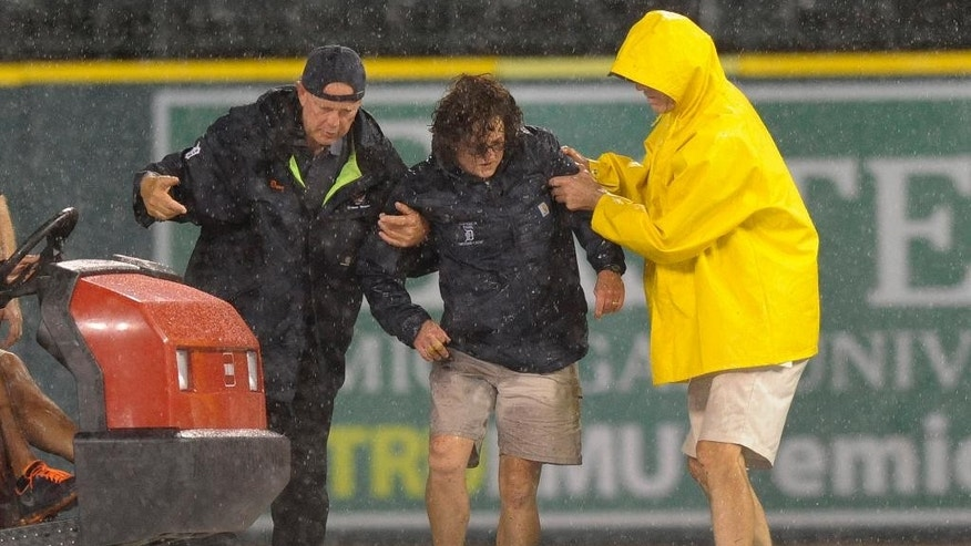 Detroit Tigers head groundskeeper Heather Nabozny, center, is helped to her feet by ground personnel after injuring herself while helping put the rain tarp on the field during a rain delay in a baseball game between the Tigers and the San Francisco Giants in the fourth inning Friday, Sept. 5, 2014, in Detroit. (AP Photo/Jose Juarez)