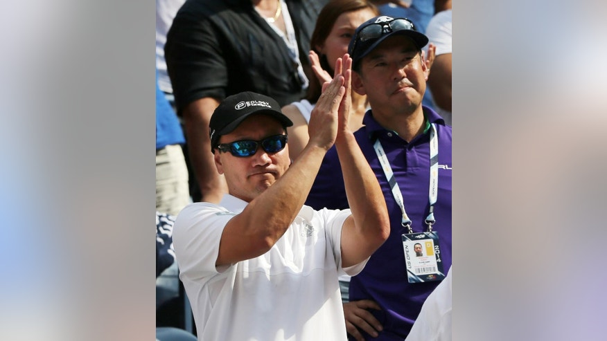 Michael Chang, coach of Kei Nishikori, of Japan, applauds after Nishikori defeated Novak Djokovic, of Serbia, during the semifinals of the 2014 U.S. Open tennis tournament, Saturday, Sept. 6, 2014, in New York. (AP Photo/Mike Groll)