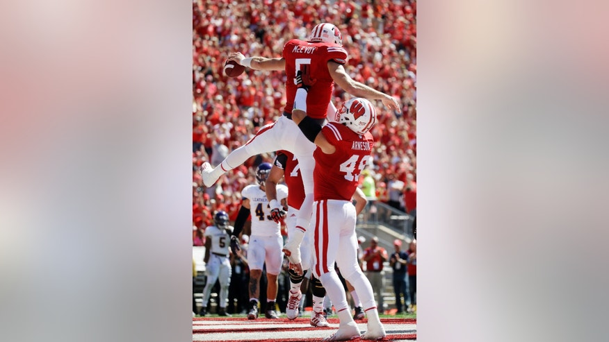 Wisconsin's Sam Arneson (49) lifts Tanner McEvoy (5) after McEvoy's touchdown run during the first half of an NCAA college football game against Western Illinois Saturday, Sept. 6, 2014, in Madison, Wis. (AP Photo/Morry Gash)