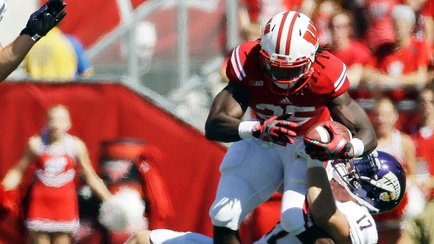 Western Illinois's Kevin Kintzel (17) stops Wisconsin's Melvin Gordon  during the first half of an NCAA college football game Saturday, Sept. 6, 2014, in Madison, Wis. (AP Photo/Morry Gash)