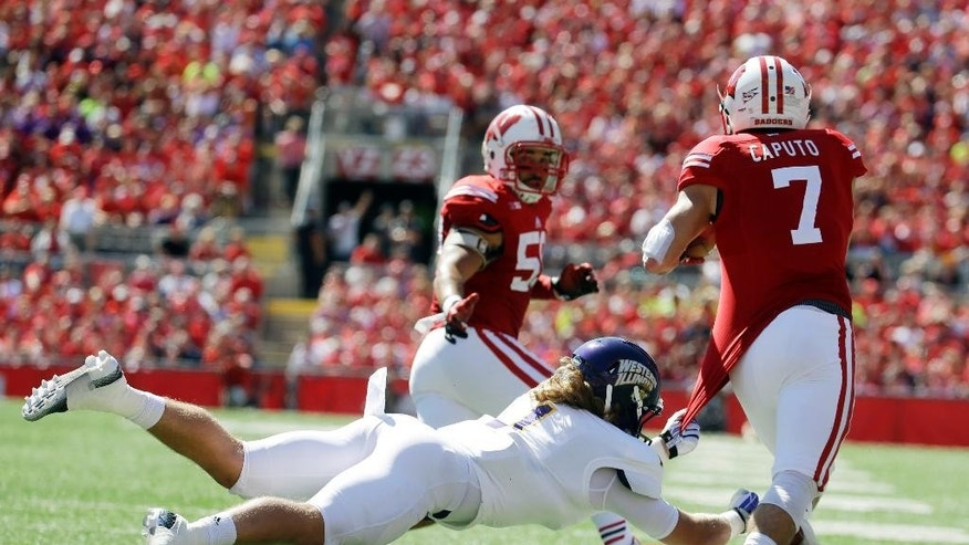 Western Illinois's Joey Borsellino (1) tries to stop Wisconsin's Michael Caputo (7) after an interception during the first half of an NCAA college football game Saturday, Sept. 6, 2014, in Madison, Wis. (AP Photo/Morry Gash)