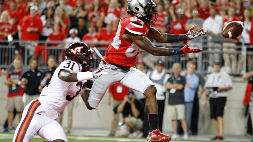 Ohio State wide receiver Corey Smith, right, drops a pass as Virginia Tech cornerback Brandon Facyson defends during the second quarter of an NCAA college football game Saturday, Sept. 6, 2014, in Columbus, Ohio. (AP Photo/Paul Vernon)