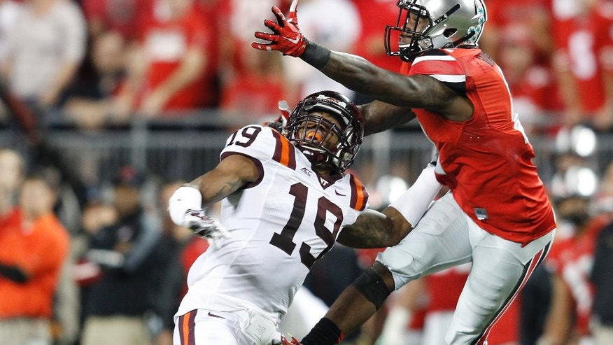 Ohio State halfback Dontre Wilson, right, makes a catch over Virginia Tech cornerback Chuck Clark during the second quarter of an NCAA college football game Saturday, Sept. 6, 2014, in Columbus, Ohio. (AP Photo/Paul Vernon)