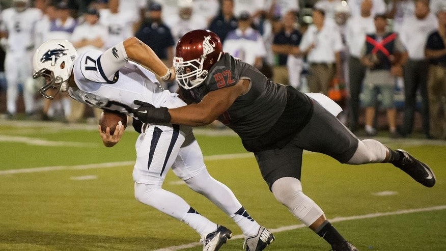 Nevada's Cody Fajardo (17) gets sacked by Washington State's Robert Barber (92) during the first half of an NCAA college football game Friday, Sept. 5, 2014, in Reno, Nev.(AP Photo/Kevin Clifford)