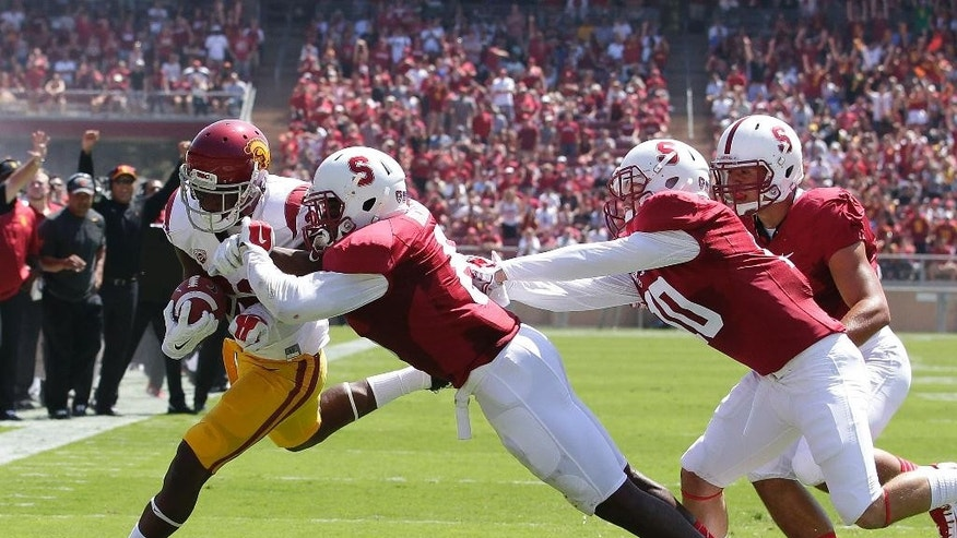 Southern California running back Justin Davis (22) rushes against Stanford safety Jordan Richards, center, and Zach Hoffpauir (10) during the first half of an NCAA college football game on Saturday, Sept. 6, 2014, in Stanford, Calif. (AP Photo/Tony Avelar)