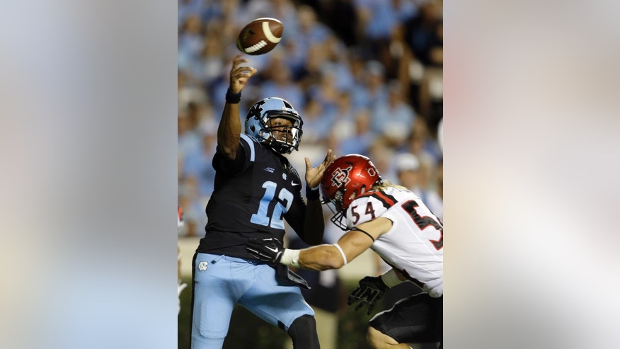North Carolina quarterback Marquise Williams (12) passes as San Diego State's Calvin Munson (54) rushes during the first half of an NCAA college football game in Chapel Hill, N.C., Saturday, Sept. 6, 2014. (AP Photo/Gerry Broome)