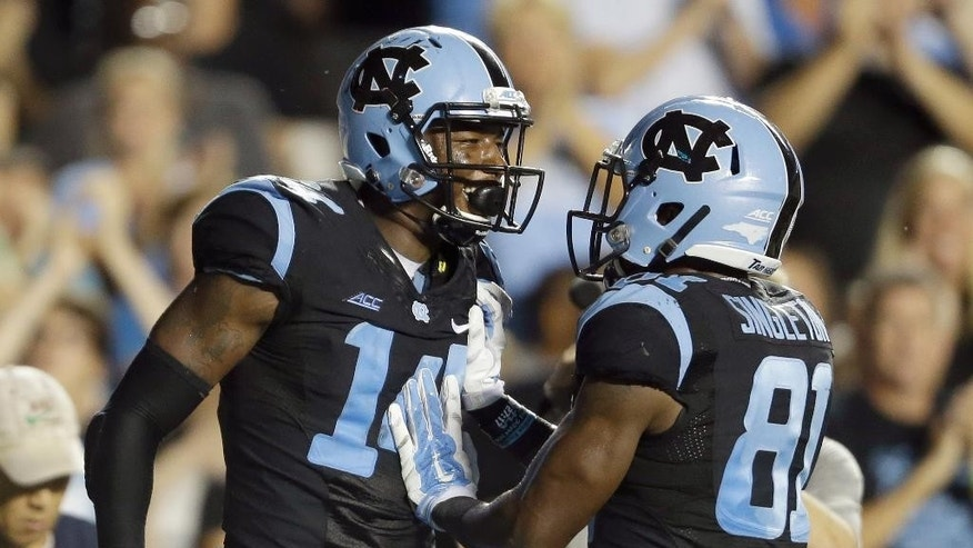 North Carolina's Quinshad Davis (14) and Kendrick Singleton (81) celebrate Davis' touchdown against San Diego State during the second half of an NCAA college football game in Chapel Hill, N.C., Saturday, Sept. 6, 2014. North Carolina won 31-27. (AP Photo/Gerry Broome)