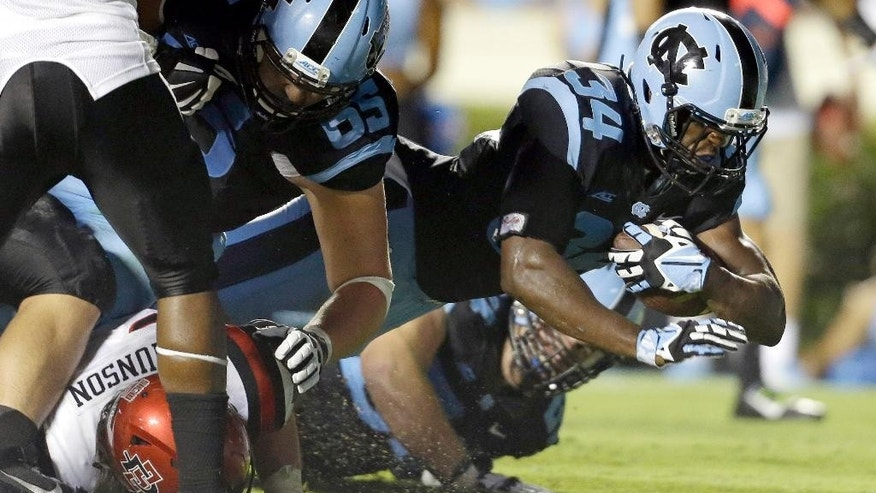 North Carolina's Elijah Hood (34) scores a touchdown against San Diego State as Jared Cohen (65) blocks during the second half of an NCAA college football game in Chapel Hill, N.C., Saturday, Sept. 6, 2014. North Carolina won 31-27. (AP Photo/Gerry Broome)