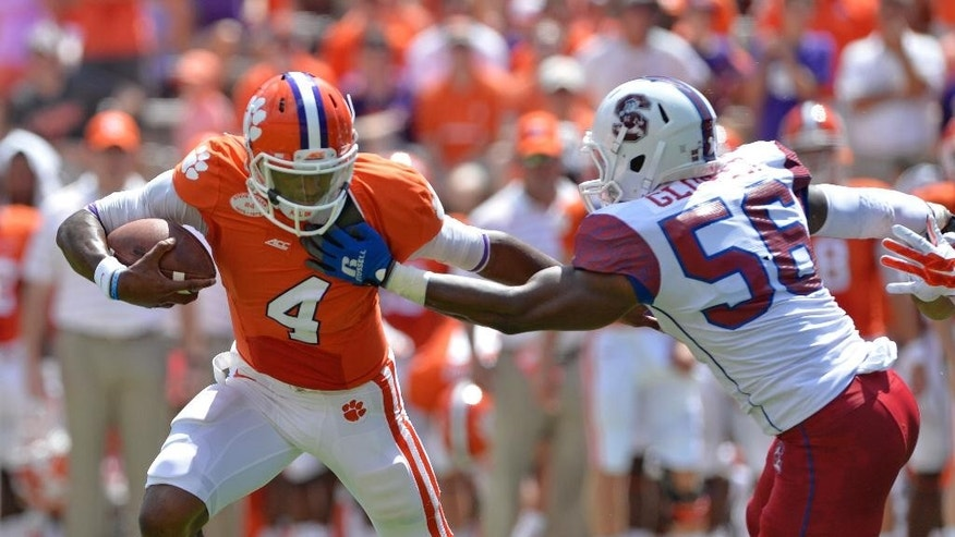 Clemson quarterback Deshaun Watson runs out of the pocket and is pressured by South Carolina State's Alexander Glover during an NCAA college football game in Clemson, S.C.,  Saturday, Sept. 6, 2014.  (AP Photo/ Richard Shiro)