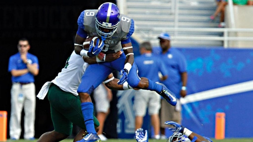 Kentucky wide receiver Demarco Robinson (9) hurdles in teammate as Ohio's Jovon Johnson (51) grabs his waist on this first half play in their NCAA college football game in Lexington, Ky., Saturday Sept. 6, 2014. (AP Photo/Garry Jones)