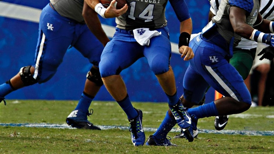 Kentucky quarterback Patrick Towles (14) makes a run up the center of the line during the first half of their NCAA college football game against Ohio in Lexington, Ky., Saturday Sept. 6, 2014. (AP Photo/Garry Jones)