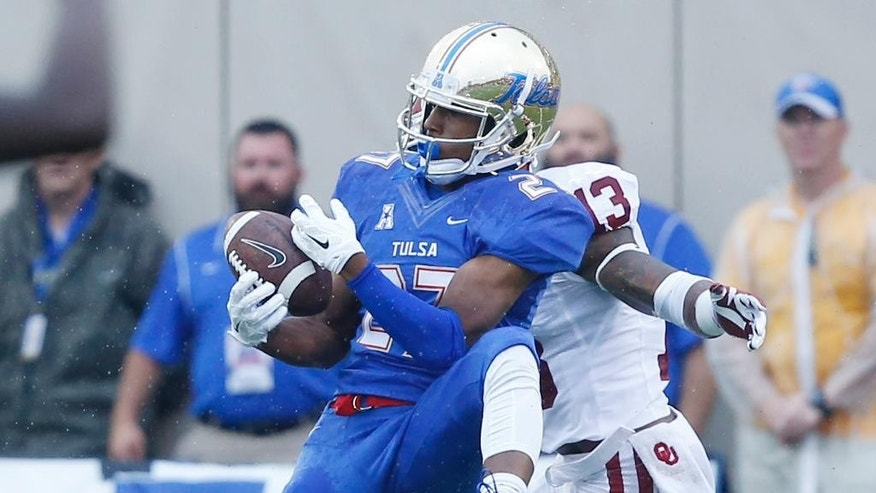 Tulsa wide receiver Bishop Louie (27) can't hold onto the pass in front of Oklahoma safety Ahmad Thomas (13) in the second quarter of an NCAA college football game in Tulsa, Okla., Saturday, Sept. 6, 2014. (AP Photo/Sue Ogrocki)