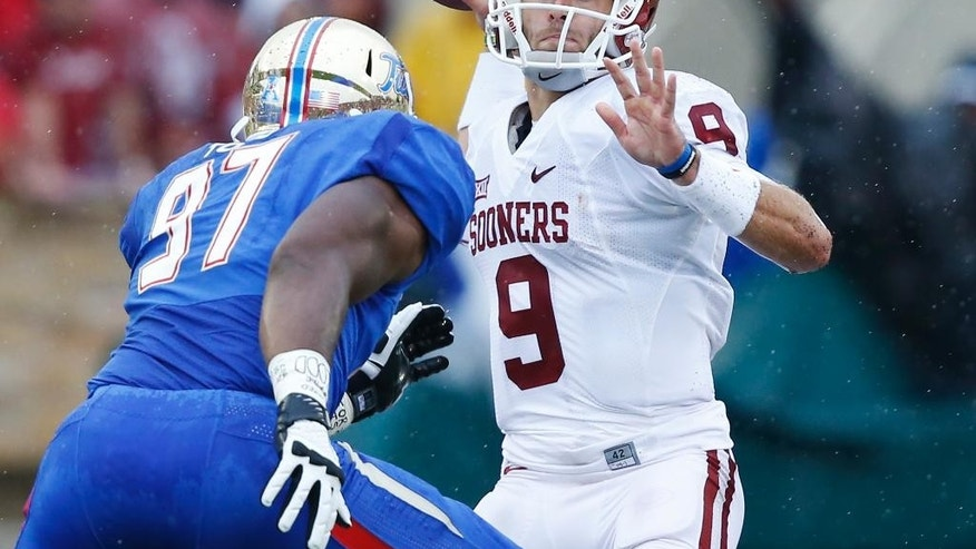 Oklahoma quarterback Trevor Knight (9) passes over Tulsa defensive end Brentom Todd (97) in the second quarter of an NCAA college football game in Tulsa, Okla., Saturday, Sept. 6, 2014. (AP Photo/Sue Ogrocki)