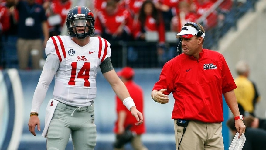 Mississippi head coach Hugh Freeze, right, talks with quarterback Bo Wallace (14) in the first quarter of an NCAA college football game against Vanderbilt, Saturday, Sept. 6, 2014, in Nashville, Tenn. (AP Photo/Mark Humphrey)