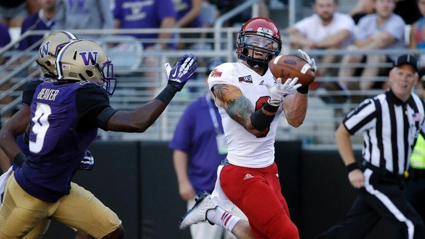 Eastern Washington wide receiver Cory Mitchell, right, catches a 28-yard touchdown pass as Washington's Brandon Beaver defends in the first half of an NCAA football game Saturday, Sept. 6, 2014, in Seattle. (AP Photo/Elaine Thompson)