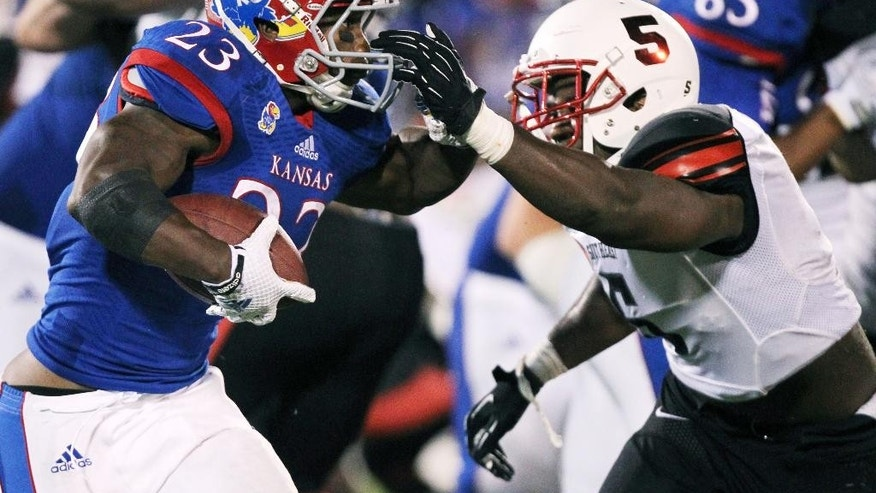 Kansas running back De'Andre Mann (23) tries to make his way around Southeast Missouri State's Wisler Ymonice (5) during the third quarter of an NCAA football game Saturday, Sept. 6, 2014, in Lawrence, Kan. Kansas won 34-28. (AP Photo/Ed Zurga)