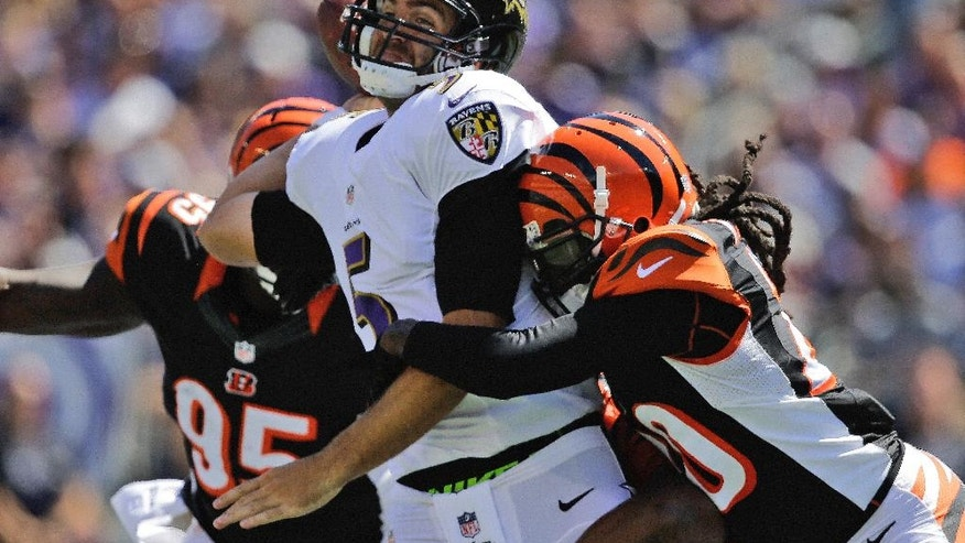 Baltimore Ravens quarterback Joe Flacco (5) is stopped by Cincinnati Bengals defensive end Wallace Gilberry (95), middle linebacker Vincent Rey (57) and free safety Reggie Nelson (20) during the first half of an NFL football game in Baltimore, Md., Sunday, Sept. 7, 2014. (AP Photo/Patrick Semansky)